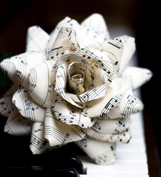 paper flower with music staves and notes on piano keyboard