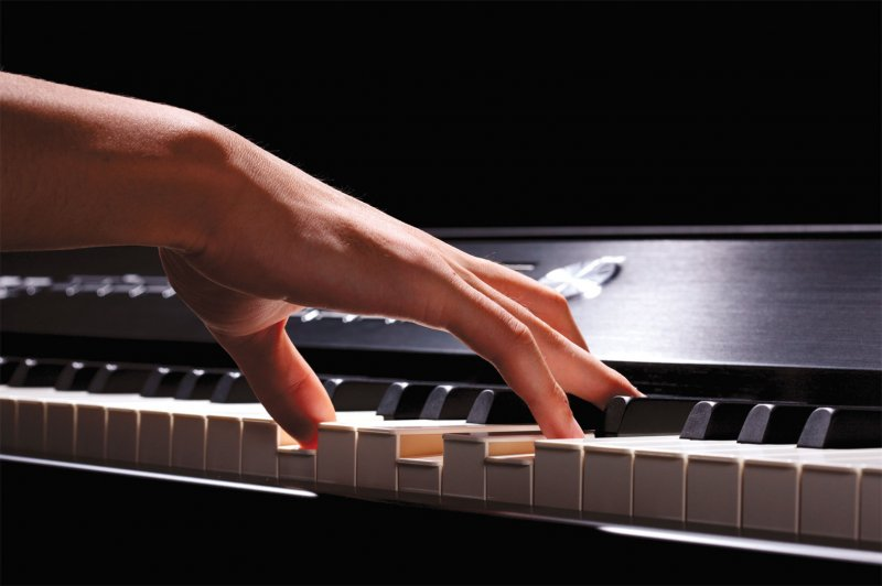 right hand playing a chord on a MIDI keyboard during online piano lesson