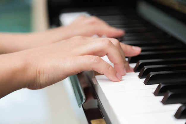 side view of two hands playing piano during online piano lesson