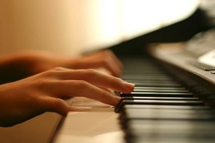 two hands playing on a MIDI keyboard during online piano lesson