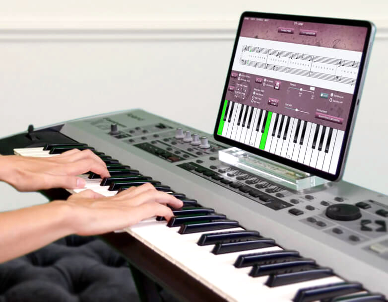 online piano lessons app on iPad with students hands on piano keyboard