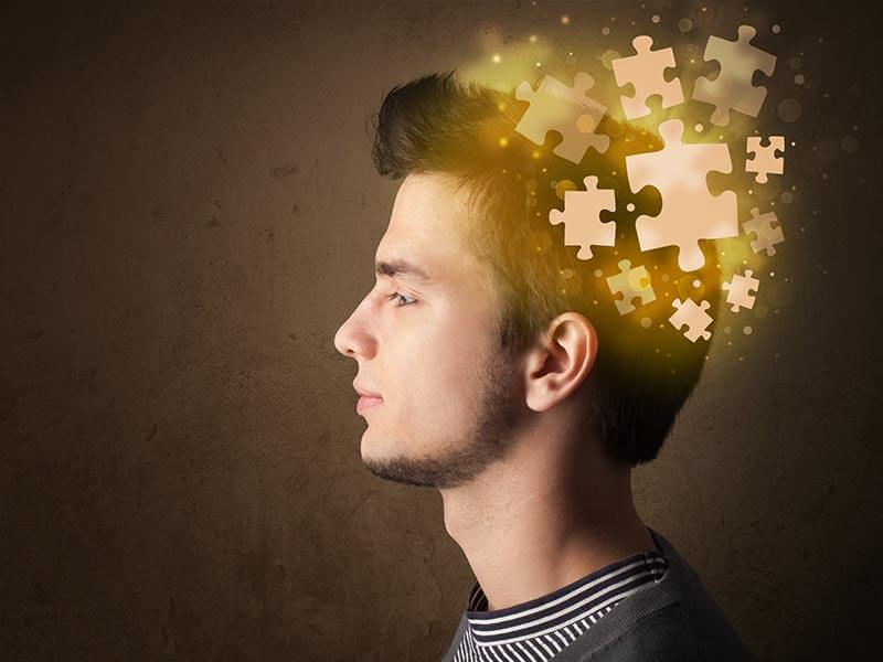 man with pieces of jig saw puzzle coming together inside his head