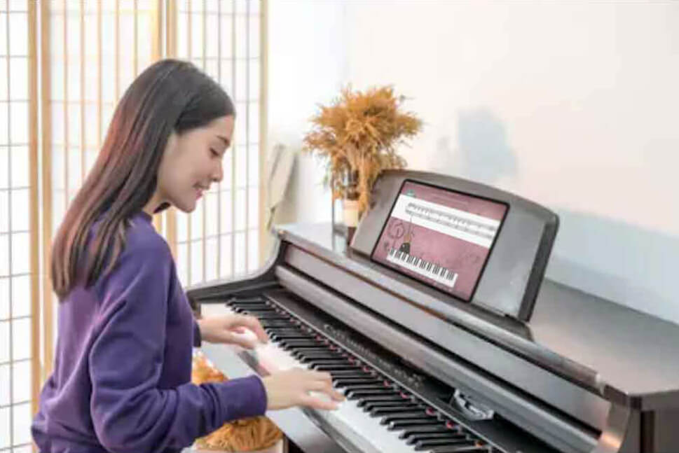 Girl at digital piano with iPad learning piano