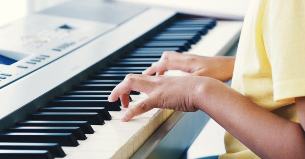 Child's hands playing digital piano