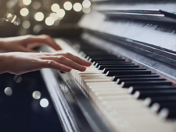 Hands playing piano keyboard