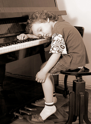 child asleep at piano
